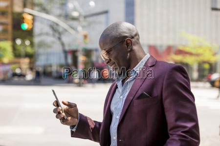 stylish businessman looking at smartphone