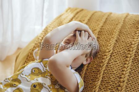 little boy lying on cushion covering