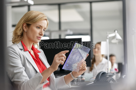 businesswoman at desk in office using