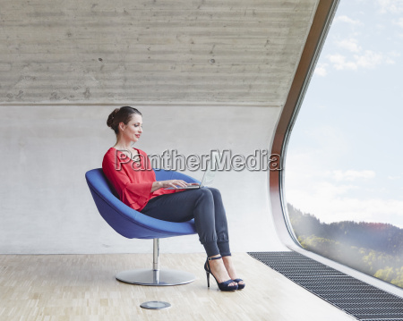 woman sitting on chair in attic