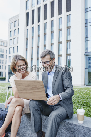 happy businesswoman and businessman sharing laptop