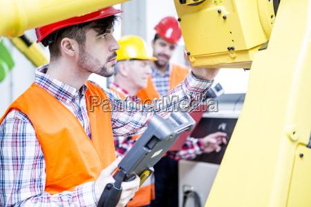 man in factory examining industrial robot