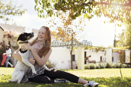 happy girl playing with dog in