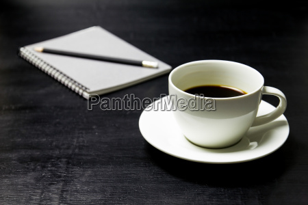 coffee with notebook and pencil on