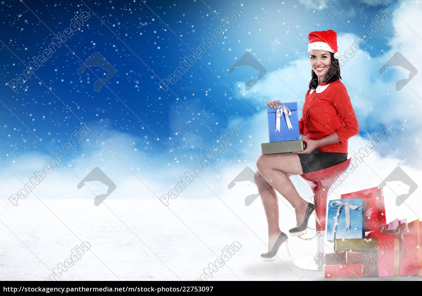 asian, woman, wearing, santa, hat, holding - 22753097
