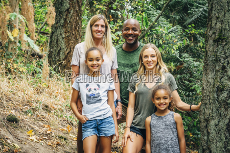 multi ethnic family posing in forest
