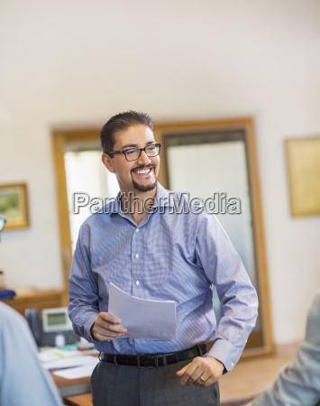 smiling hispanic businessman holding paperwork in