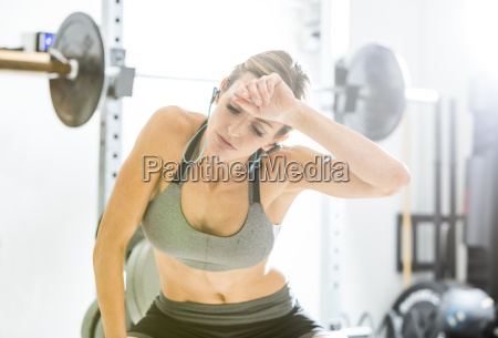 woman resting in gymnasium wiping sweat