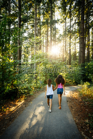 mixed race sisters holding hands walking