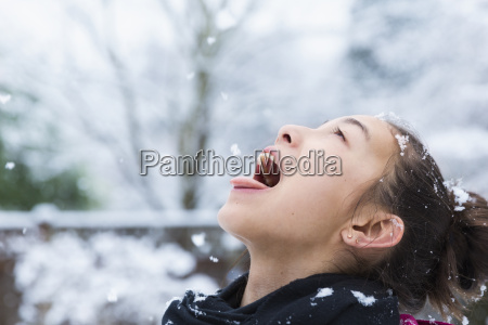 mixed race girl catching snowflakes on