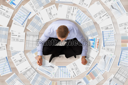 businessman, doing, meditation, surrounded, with, documents - 22763813