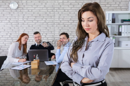 colleagues, laughing, to, her, coworker, in - 22763753