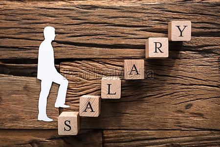 paper businessman climbing salary block ladder