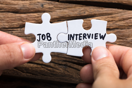 hands connecting job interview jigsaw pieces