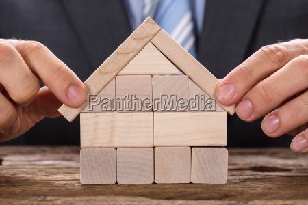 businessman making model house with wooden