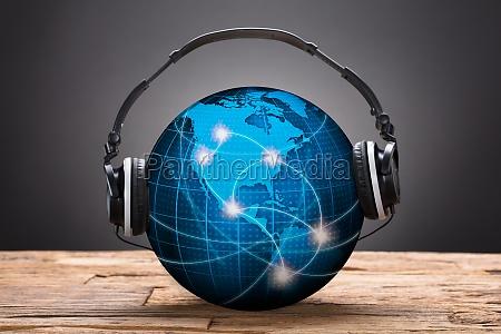 headphones on blue globe against black