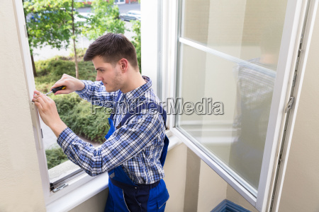 handyman fixing window with screwdriver