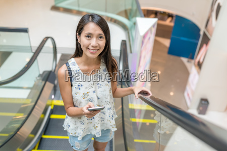 woman holding cellphone on escalator in