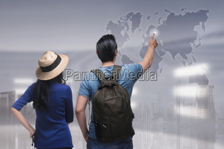 portrait of asian couple traveler pointing