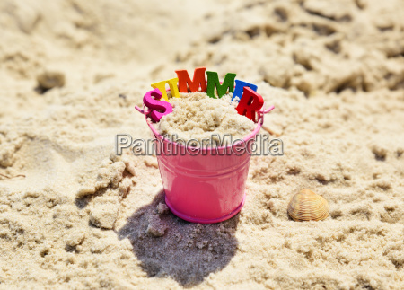pink metal baby bucket with sand