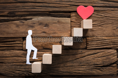 paper man climbing steps leading towards