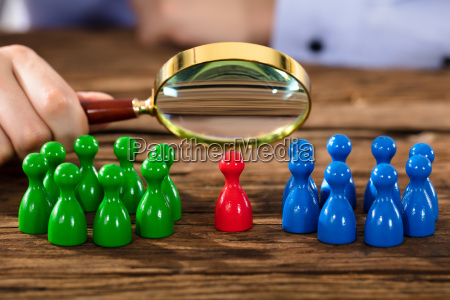 person examining figures with magnifying glass