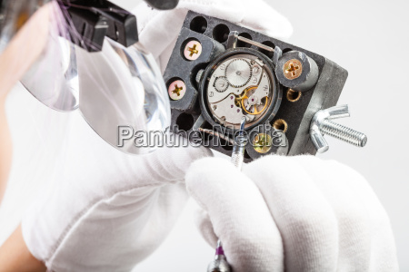 watchmaker in magnifying glasses repairs old