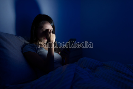 woman feeling headache bed with mobile