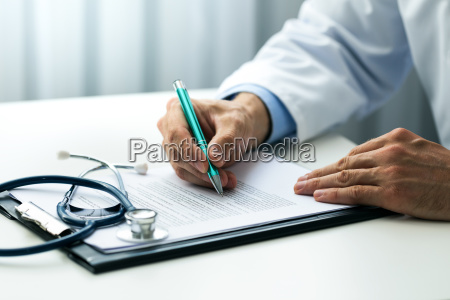 doctor writing documents at desk in