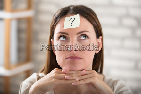 businesswomans forehead with question mark on