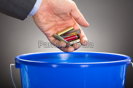 businessmans hand throwing old batteries in