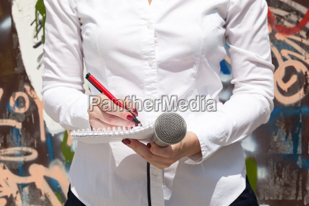 female journalist at news event writing