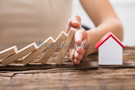 human hand stopping the wooden blocks