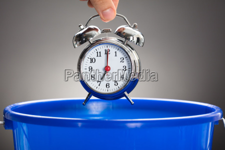 businessmans hand throwing alarm clock in