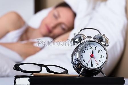 eyeglasses and alarm clock on table