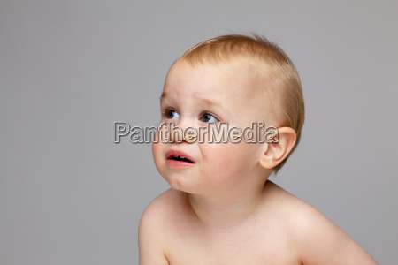 cute baby boy looking away while