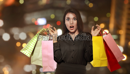 emocionado asiatico mujer sosteniendo colorido bolsa