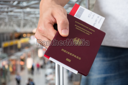 person with luggage holding passport and