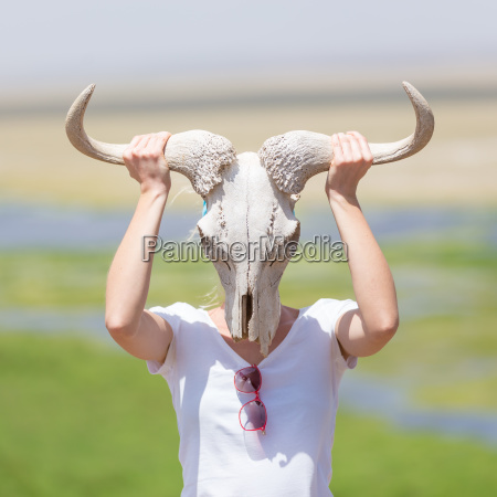 woman holding a white wildebeest skull