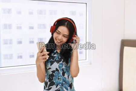 happy asian woman listening music with