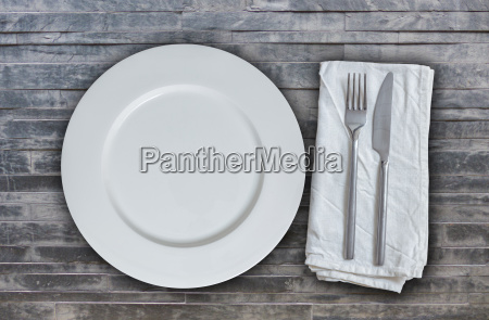 empty plate with cutlery on stone