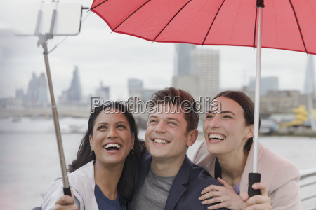 smiling friend tourists with umbrella taking