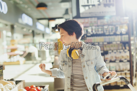 young woman with headphones browsing grocery