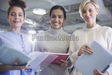 portrait smiling confident businesswoman with paperwork