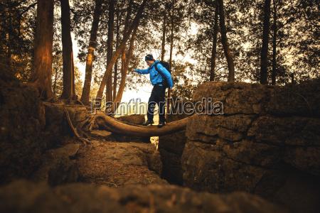 male hiker crossing abyss over fallen