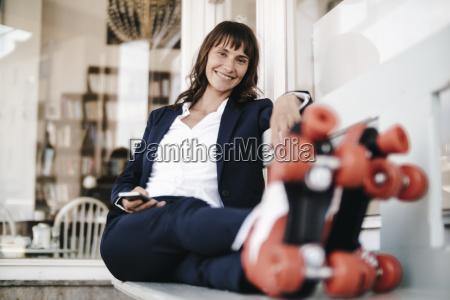businesswoman wearing roller skates holding smartphone