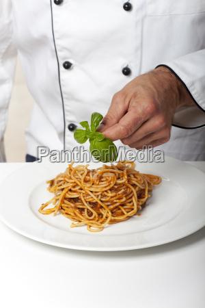 chef decorates a pasta dish