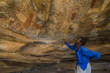 guia apontando para pinturas rupestres em