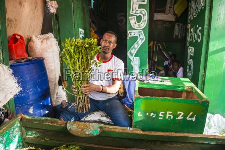 man selling khat in the market