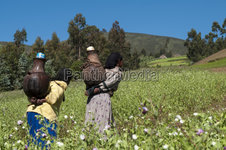 two women walk through the fields